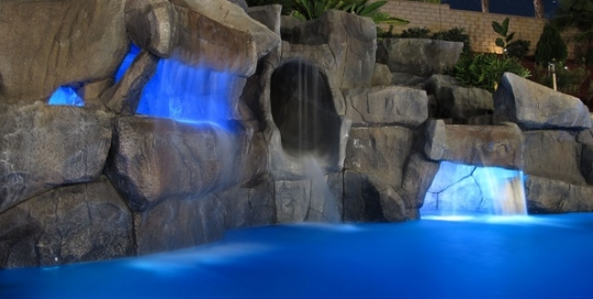 Artificial rock cavern, waterfall, slide, and pool in California.